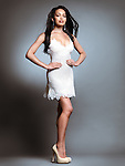 Fashion photo of a beautiful young black woman wearing short white dress isolated on gray background