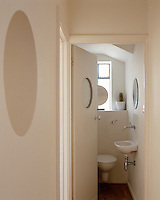 A downstairs cloakroom echoes the nautical theme of the house with its porthole window and circular mirrors