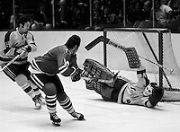 Seals Gilles Meloche makes a save against Chicago Black Hawks Bryan Campbell, Rick Smith #5 rushes to help. (photo copyright Ron Riesterer)
