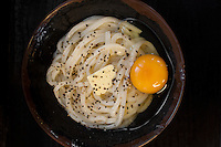 Hot udon with butter, egg, and black pepper at Bakaichidai - a signature dish that mixes to a creamy carbonara.