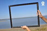 Boy's hand holding picture frame on beach  (Licence this image exclusively with Getty: http://www.gettyimages.com/detail/83154254 )