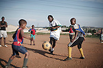 "SOWETO, SOUTH AFRICA - OCTOBER 23: Zacharia ""Computer"" Lamula, an old football star in the local team Kaizer Chiefs teaches young boys his skills on September 15, 2007 in the Diepkloof section of Soweto, South Africa. Soccer is the most popular sport in South Africa, and a because of the upcoming World Cup 2010, the interest is increasing. For the first time the World Cup will be held on the African continent. South Africa doesn't have an organized youth soccer program and many teams and players struggle with lack of funds to buy equipment and securing money for transport to games. (Photo by Per-Anders Pettersson)....."