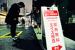 """A sign informs passerby of the AIDS test offered free-of-charge by a doctor of an HIV awareness group at a bar in Tokyo, Japan. Gynaecologist Dr Tsuneo Akaeda, who visits the Tokyo bar as part of the Girl's Guard volunteer group, says the number of HIV infection rates surged in 2008 to about 5,000 compared with 1,500 a year earlier. """"The figure is probably much higher because there are people who probably have it but are too scared to be diagnosed,"""" Akaeda says. """"Awareness in Japan is on the 'it couldn't happen to me' level,"""" says a customer who undertook the test offered by Akaeda at the Club Jamaica bar in Tokyo's notorious Roppongi entertainment district."""