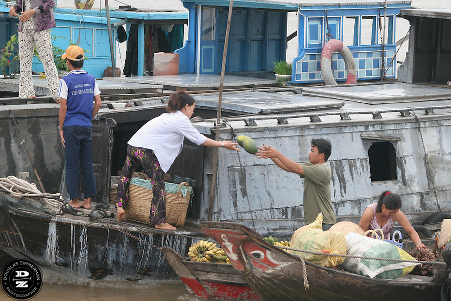 Produce wholesalers deliver fruits to a waiting  motorboat passenger on the Bassac River in the Mekong Delta in Chau Doc, Vietnam.  The Mekong Delta has long been the watery  thoroughfare for the many villages that dot the riversides of the delta. Many of the villages have floating markets where people can buy produce and other items from wholesalers.  Photograph by Douglas ZImmerman