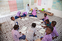 Jambiani, Zanzibar, Tanzania.  Primary School Classroom with Students and Teacher.  Students sit on the floor since the school has no furniture.  The workbook, in Swahili, is about eating foods strong in protein, to build strong bodies.