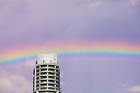 A rainbow appears in the sky behind a Miami condo building.