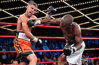 Madison Square Garden, New York, Oct. 10th,2009: Rogers Mtagwa (white trunks) lands  on Juan Manuel Lopez during their 12 rounds WBO Jr. Featherweight Title fight. Lopez won a narrow unanimous decision, remaining unbeaten (27-0) and keeping his title. Photo by Thierry Gourjon.