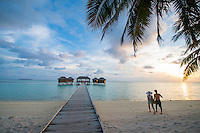 Maldives, Rangali Island. Conrad Hilton Resort. Little girl walking down the boardwalk to the spa at sunset.