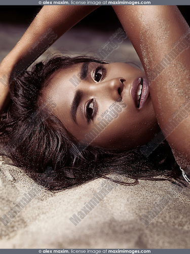 Artistic sensual portrait of a young woman lying on sand at night, closeup of face