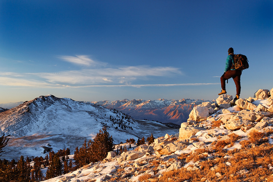 Male hiker in White Mountains at sunrise (Sierra Mountains in background), Inyo National Forest, White Mountains, California, USA