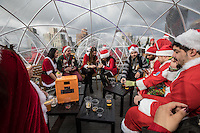 NEW YORK, NY - December 10: Revelers dressed as Santa Claus drink on the roof top of a bar during the annual SantaCon event in New York City , December 10, 2016.VIEWpress/Maite H. Mateo