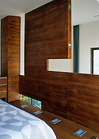 The wooden wall panels of this mezzanine bedroom are hinged and can be folded back to allow more sunlight through the double-height windows in the main room