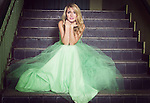 Young lady with blonde hair in a vintage dress sitting at old stairs and looking in the front of the camera