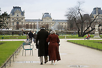 Elderly couple take a calm stroll arm in arm through Jardin des Tuileries by the Louvre Museum art gallery, Central Paris, France