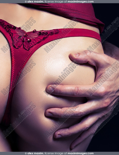 Artistic erotic closeup of a man hand on buttocks of a sexy young woman in red underwear