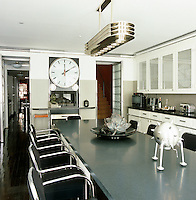 The contemporary monochrome kitchen has clocks showing Los Angeles, Paris and New York time