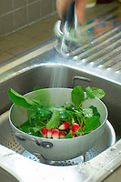 Radishes are washed in a colander for a simple spring lunch