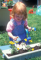 Cute little girl with red hair, blue overalls, pink shirt, gardening with yellow marigolds flowers, blue play shovel trowel and runner box of flowers, on lawn