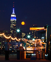People visit a pier in Hoboken while a full moon rises next to the Empire State Building in New York City,  Aug 21, 2013. Photo by Eduardo Munoz Alvarez / VIEWpress.