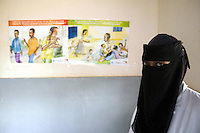 Somaliland. Waqohi Galbed province. Hargeisa. Tubeculosis (TB) hospital. Portrait of a  black muslim nurse, wearing a black veil on her hair and on her face ( traditional moslem cloth called nikab). Prevention poster for TB transmission are taped on the wall. The Global Fund through the ngo ( Non-governmental organization ) World Vision supports the programm with a Tuberculosis grant (financial aid). Somaliland is an unrecognized de facto sovereign state located in the Horn of Africa. Hargeisa is the capital of Somaliland. © 2006 Didier Ruef