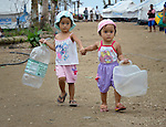 Rica May Marcha (left), 3, and her sister Ria May, 1, on their way to fetch water for their family on Jinamoc Island, part of the municipality of Basey in the Philippines province of Samar that was hit hard by Typhoon Haiyan in November 2013. The storm was known locally as Yolanda. The ACT Alliance has been providing a variety of assistance to survivors here, and is planning a long-term rehabilitation program with residents.