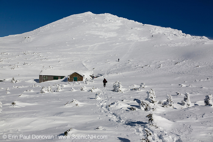 A winter hiker traveling north on the Appalachian Trail during the winter months in the White Mountains, New Hampshire. Mount Madison is in the background. And Madison Spring Hut is in view.