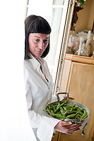 Chef Maddalena Caruso carrying a colander filled with freshly picked peas ready to be shelled