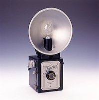 VINTAGE BOX CAMERA WITH FLASHBULB REFLECTOR<br /> One Of The Simplest Cameras<br /> Essentially a box with a lens on one side and film on the other, a box camera usually has a single element focus free lens and lacks aperture and shutter speed controls. Magnesium elements in the flashbulb were electrically ignited to create a flash.