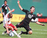 Carey Talley #8 of D.C. United falls after a tackle from Joel Lindpere #20 of the New York Red Bulls during an MLS match on May 1 2010, at RFK Stadium in Washington D.C.