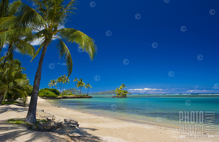 Sunny day with blue sky and white sand at Kahala Beach with little island off shore,Honolulu,Oahu