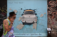 Man walking past a section of the Berlin Wall depicting a painting of a Trabant car bursting through the wall entitled Test the Best (Test the Rest) by Birgit Kinder, part of the East Side Gallery, a 1.3km long section of the Wall on Muhlenstrasse painted in 1990 on its Eastern side by 105 artists from around the world, Berlin, Germany. Picture by Manuel Cohen