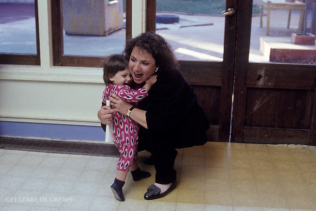 Berkeley CA Mother greeting daughter, age two, while picking her up at day care