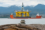 A rock cairn left on a log on Ediz Hook in Port Angeles. In the background is the 400 foot tall Polar Pioneer, an oil drilling platform brought in from Asia piggybacked on a large ship, on its way to Seattle and maybe Alaska.