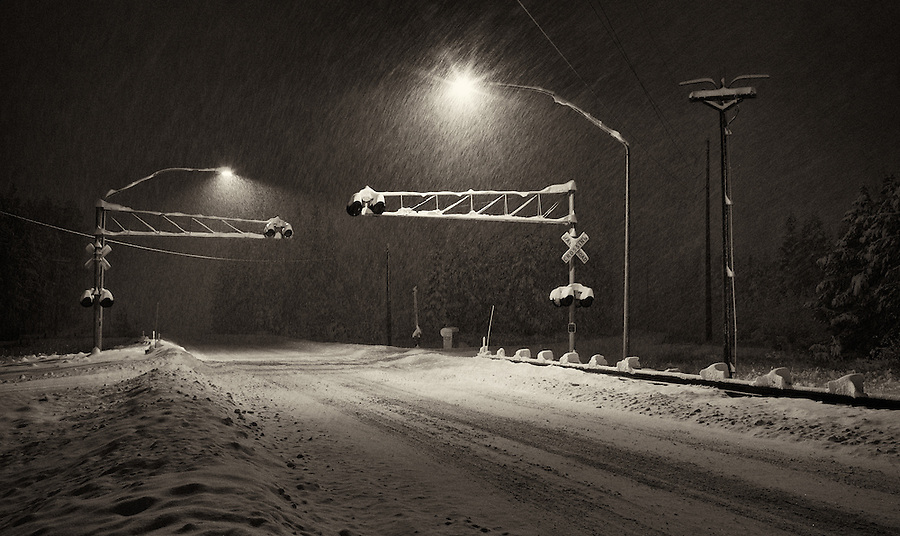 Snow falls at a dark and remote railroad crossing in the evening.