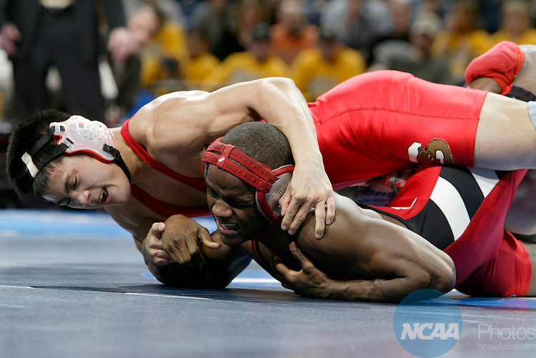 17 MARCH 2005:  Travis Lee (left, in white headgear) of Cornell  University wrestles with Shawn Bunch (red headgear) of Edinboro College during the 133 pound championship match at the 2005 NCAA Division 1 Men's Wrestling Championships at Savvis Center in St. Louis, MO. Lee defeated Bunch by a score of 6-3 for the championship title.   Mark Buckner/NCAA Photos