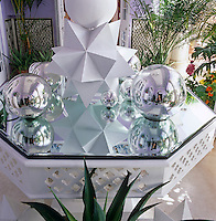 Interesting reflections are cast on the glass-topped veranda table by the custom-made polyhedra and mirrored baubles