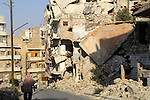A Syrian man walks past the rubble of buildings which destroyed by forces of Syria's President Bashar al-Assad, in a rebel-controlled area in the northern Syrian city of Aleppo, on August 31, 2015. Photo by Ameer al-Halbi