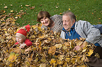 Happy Elderly Seniors Grandparents with Kid Girl in Autumn Leaves