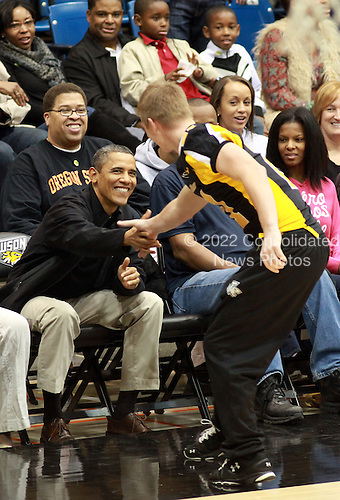 United States President Barack Obama shakes hands with a member of the Towson Tigers football team during the Towson State University - Oregon State University basketball game on the campus of Towson State University in Towson, Maryland, Saturday, November 26, 2011..Credit: Martin Simon / Pool via CNP