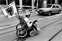 Switzerland. Zürich. A young soccer fan from the FC Aarau football club rides the road on his wheelchair moved by an electric engine.  He crosses a VW golf car. © 1990 Didier Ruef