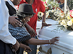 A woman reaches out to touch a casket during a January 23 funeral mass for the Roman Catholic archbishop and vicar general of Port-au-Prince, both of whom were killed in the country's earthquake.