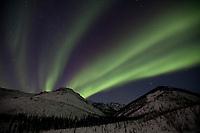Aurora borealis arcs over the White Mountains in the White Mountains National Recreation Area, interior, Alaska.