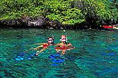 A couple wearing snorkel gear tread water in the beautiful clear turquoise water of Kealakekua Bay.