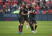 Toronto, Ontario - May 3, 2014: Toronto FC midfielder Jackson Goncalves #11 celebrates his goal with Toronto FC forward Gilberto #9 and Toronto FC midfielder Kyle Bekker #8 during a game between the New England Revolution and Toronto FC at BMO Field.
