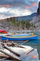 Early morning comes to Moraine Lake in Banff National Park. I visited this site 5 mornings in a row and only once did I have partly cloudy skies. All other times it was cloudy and rainy. This Rocky Mountain image features boats resting quietly with the Rockies rising in the background.
