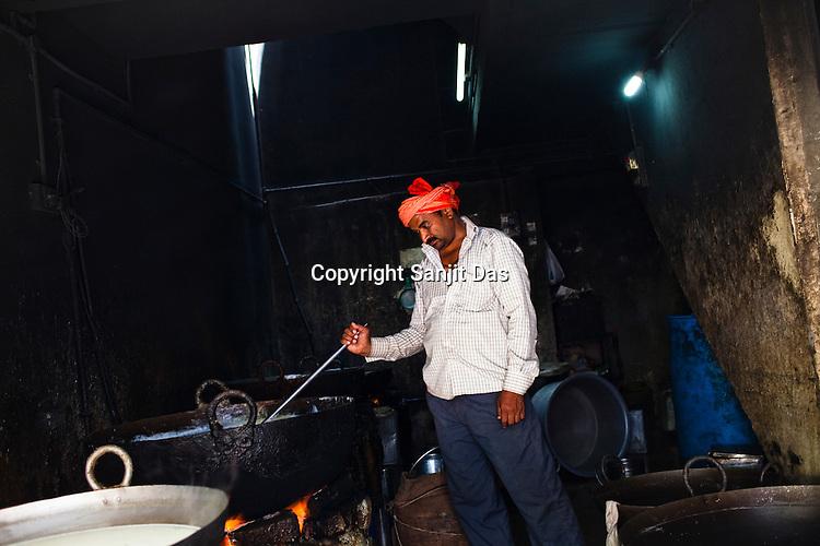 A vendor boils milk in big woks in the ancient city of Varanasi in Uttar Pradesh, India. Photograph: Sanjit Das/Panos