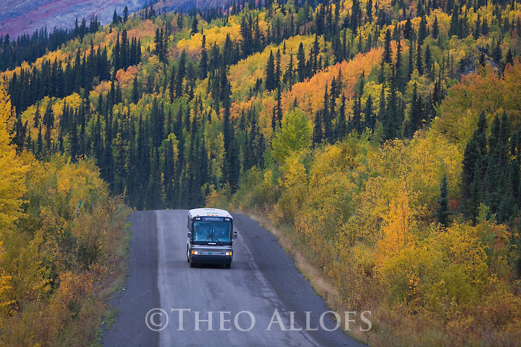 Tour bus on Dempster Highway in fall; a gravel road between Dawson City and Inuvik/NWT at the eastern side of the Mackenzie Delta