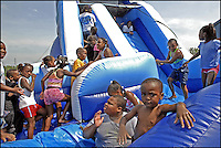 Children play on an inflatable slide at Keith High School in Orrville, Ala.