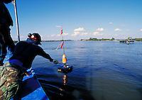Workmen are retrieving a solar powered DAU (Data Acquisition Unit.). Louisiana, Marsh Island.