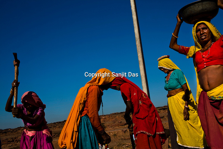 Women work at a site as part of NREGA at Nazir ka Mandir in Karauli district of Rajasthan, India. The National Rural Employment Guarantee Act (NREGA) that has created a source of additional income for families living below the poverty line by providing a minimum 100 days of employment assured under the Act. Photo by Sanjit Das